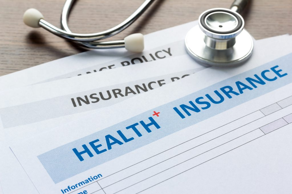 Close up of stethoscope laying on health insurance forms.